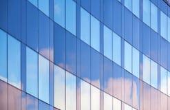 Nice molnreflexioner i fönster av kontoret Arkivbild
