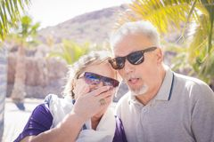 Nice faces for a couple of seniors. Nice faces laughing for an elderly couple in vacation. Palms and sunlight and they wear sunglasses. Nice and funny life Royalty Free Stock Photo