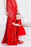 Nice, familie, goede foto van moeder en dochter in rood kleedt zich in de studio Moederdag en dochters stock afbeelding