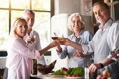 Nice family celebrating together in the kitchen. Raise your glasses. Big lovely family having their drinks in a cozy kitchen while celebrating the holiday Stock Images