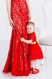 Nice, family, good photo of mother and daughter in red dresses in the studio. Mother`s Day and daughters. stock image