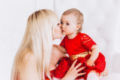 Nice, family, good photo of mother and daughter in red dresses in the studio. Mother`s Day and daughters. royalty free stock photo