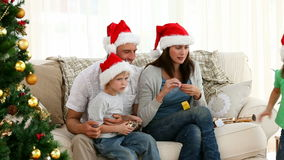 Nice family opening Christmas gifts while sitting on the floor Stock Photo