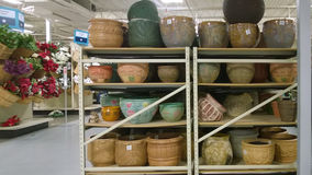 Nice flowerpots  on shelves selling Stock Photography