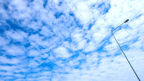 Nice Fluffy clouds filled the sky and the light pole while Royalty Free Stock Photos