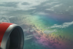 Nice  fragment of a view from on aircraft climbing above rainbow beautiful color clouds that bring attention Royalty Free Stock Image
