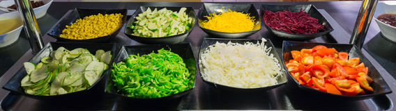 Nice fragment of view of beautiful appetizing fresh vegetable salads in dark ceramic plates Royalty Free Stock Images