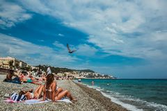 NICE, FRANCE - JUNE 26, 2017: People enjoying sunny weather on the beach of Mediterranean sea stock photography