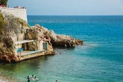 NICE, FRANCE - JUNE 26, 2017: People enjoying sunny weather on the stone beach of Mediterranean sea in Nice, near the Promenade de stock photography