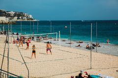 NICE, FRANCE - JUNE 26, 2017: People enjoying sunny weather on the stone beach and playing beach volleyball in Nice, near the Prom stock photo