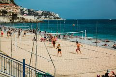 NICE, FRANCE - JUNE 26, 2017: People enjoying sunny weather on the stone beach and playing beach volleyball in Nice, near the Prom stock images