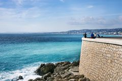 Nice, France, March 2019. Panorama. Azure sea, waves, English promenade and people resting. Rest and relaxation by the sea. On a. Sunny warm day, blue waves royalty free stock photos