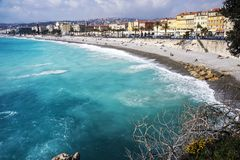 Nice, France, March 2019. Panorama. Azure sea, waves, English promenade and people resting. Rest and relaxation by the sea. On a. Sunny warm day, blue waves royalty free stock photography