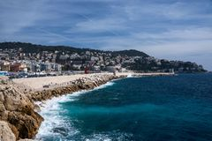 Nice, France, March 2019. Panorama. Azure sea, waves, English promenade and people resting. Rest and relaxation by the sea. On a sunny warm day, blue waves stock photography