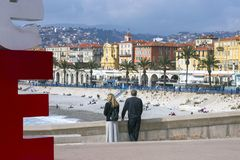 Nice, France, March 2019. Panorama. Azure sea, waves, English promenade and people resting. Young couple: a man and a woman look. At the city. Rest and royalty free stock photos