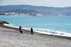 Nice, France, March 2019. Two fishermen fishing with fishing rods on the pebble beach of Nice. Cote d`Azur. Light fog hangs over stock photos