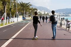 Nice, France, March 2019. Two young people: a boy and a girl ride a skateboard along the promenade. Cote d`Azur. La Croisette royalty free stock images