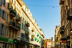 Nice, France - 2019. Narrow street in old part of Nice. Shops, restaurants, people walking around royalty free stock photography