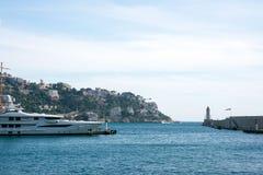 Nice, Frankrijk, Maart 2019 Azuurblauwe overzees, jachten, vuurtoren Haven en parkeren van priv? jachten in Nice Het luxueuze com royalty-vrije stock afbeelding
