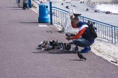 Nice, Frankrijk, Maart 2019 Voor een warme zonnige dag, voedt een mens de duiven van de stad met brood tegen het turkooise overze stock fotografie