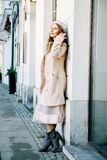 Nice Frenchwoman on the streets of the city. The girl walks around the city. An early walk. A young woman speaks through the phone and sends sms Royalty Free Stock Images