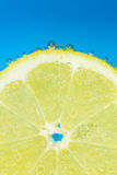 Nice fresh lemon covered with bubbles on blue background. Nice fresh lemon covered with bubbles in soda water on blue background Stock Photo