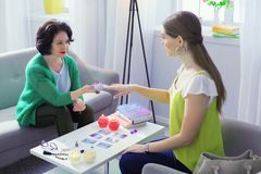 Nice friendly fortune teller looking at her client stock photography