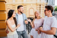 Nice friends are standing together in front of each other and talking. Bearded guy is holding a cup f coffee and royalty free stock images