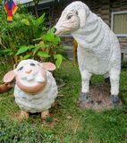 Nice funny animal figures of sheep in asian garden. Nice funny colorful welcoming figures of smiling boy girl and animal in asian pagoda garden Stock Photos