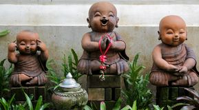 Nice garden figures of small monks in asia. Nice funny colorful welcoming figures of smiling boy girl and animal in asian country Stock Photography