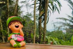 Nice funny welcome figure in asian tropical garden. Nice funny colorful welcoming figures of smiling boy girl and animal in asian pagoda garden Stock Image