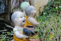 Nice funny welcome figure in asian tropical garden. Nice funny colorful welcoming figures of smiling boy girl and animal in asian pagoda garden Royalty Free Stock Photo