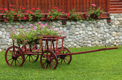 Nice garden. Nice and colorful garden with a wooden wagon Stock Images