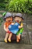Nice garden figure of smiling boy and girl. In the green grass garden Stock Photos