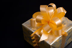 Nice gift packed in golden paper on black Royalty Free Stock Photography