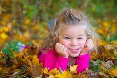 Nice girl in autumn foliage Stock Image