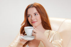 Nice girl in beige home dressing gown with a cup of coffee Stock Photography