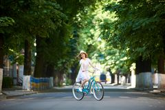Nice girl on bike alone at road. Summer sunny day. A nice girl on a bike alone on the road. Juicy city greens, vintage blue bicycle, a girl dressed in a light royalty free stock image