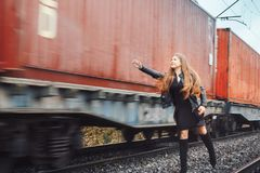 Nice girl on a railway road near moving train. Nice girl in a black dress on a railway road near moving train Royalty Free Stock Photo