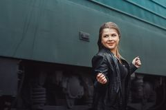 Nice girl on a railway road near moving train. Nice girl in a black dress on a railway road near moving train Royalty Free Stock Photography