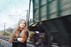 Nice girl on a railway road near moving train. Nice girl in a black dress on a railway road near moving train Royalty Free Stock Photos
