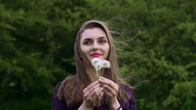 Nice girl blowing the bouquet dandelion in the garden. Slow motion.  stock footage