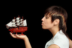 Nice girl blows on a toy ship Royalty Free Stock Photo