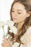 Nice girl with a bouquet of flowers. Nice girl in a white dress is holding a bouquet of spring flowers. She stands by the window with her eyes closed Stock Photography