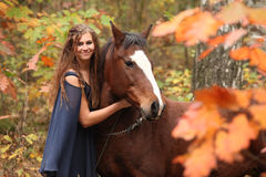 Nice girl with brown horse in autumn Royalty Free Stock Photos