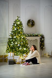 Nice girl the brunette sits about the Christmas tree. Stock Images