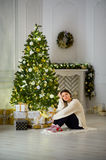 Nice girl the brunette sits about the Christmas tree. Royalty Free Stock Photos
