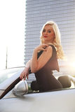 Nice girl in cabriolet car. Nice girl in a black frock standing in a cabriolet car on a street stock images