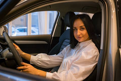 Nice girl in a car shop Royalty Free Stock Photos