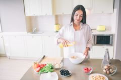 Nice girl is cooking in kitchen. She is mixing ingredients for salad in bowl. Girl is calm and concentrated. stock photos